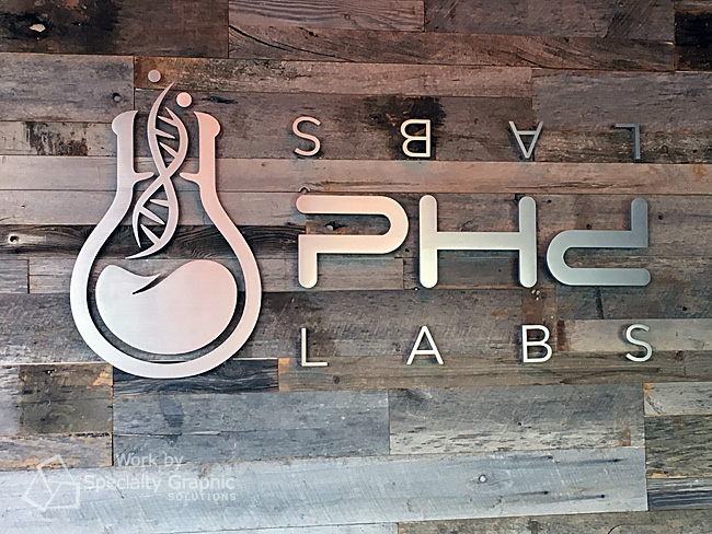 Flat cut brushed aluminum sign on reclaimed wood wall