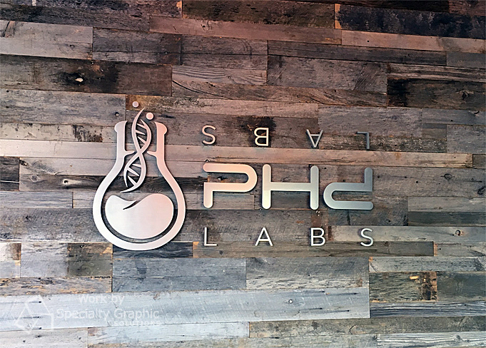 PhD Labs of Irvine CA makes a solid statement with flat cut brushed aluminum entrance sign on a reclaimed wood wall.jpg