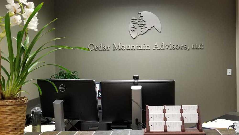 metal logo with tree cut out and company name on reception wall.jpg
