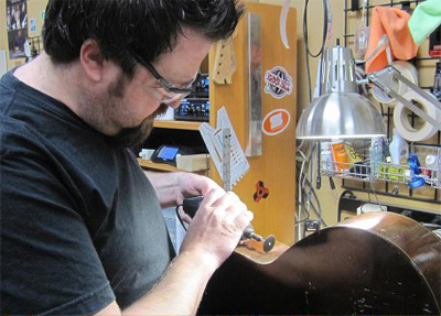 Hugh cutting a hole for a preamp/EQ box