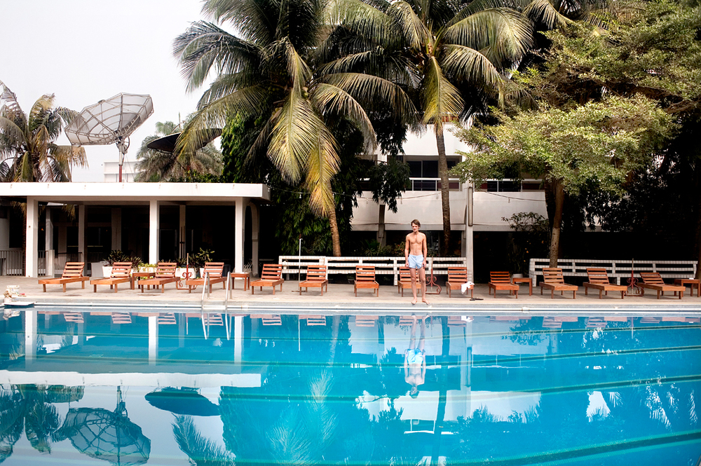 Cotonou, Benin.  Dutch tourist at the pool of a hotel.