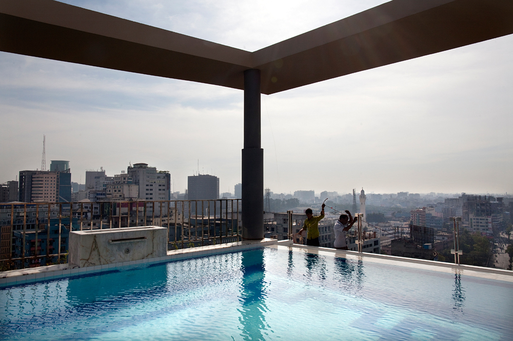 Dhaka, Bangladesh.  Construction workers at the end of the infinity pool on the 10th floor of a hotel.