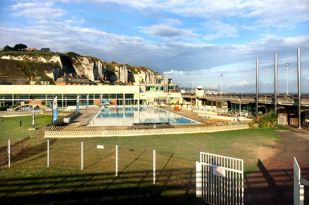 Dieppe, France.  Public  s wimming pool in the early morning sun, with on the background the famous chalk rocks.
