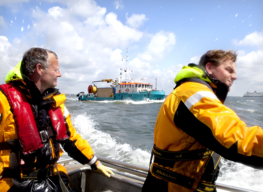 Employees working for Alliander, on a boat in the wadden sea.   Use: Magazine, Intern/Extern use.   Cliënts: Alliander