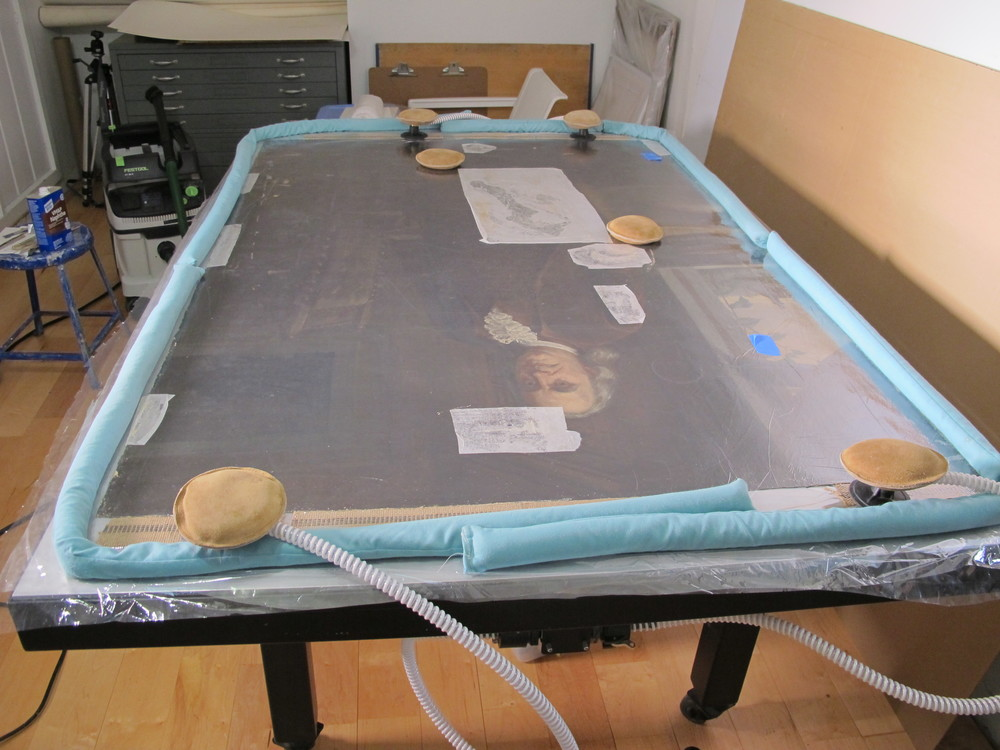 The painting was placed face up on a heat/suction table to reduce distortions/undulations of the canvas.  The table applies even heat and pressure to allow the undulations to relax.