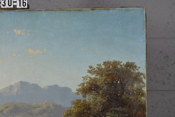 After treatment photo of a landscape with a round tear in the upper right corner.