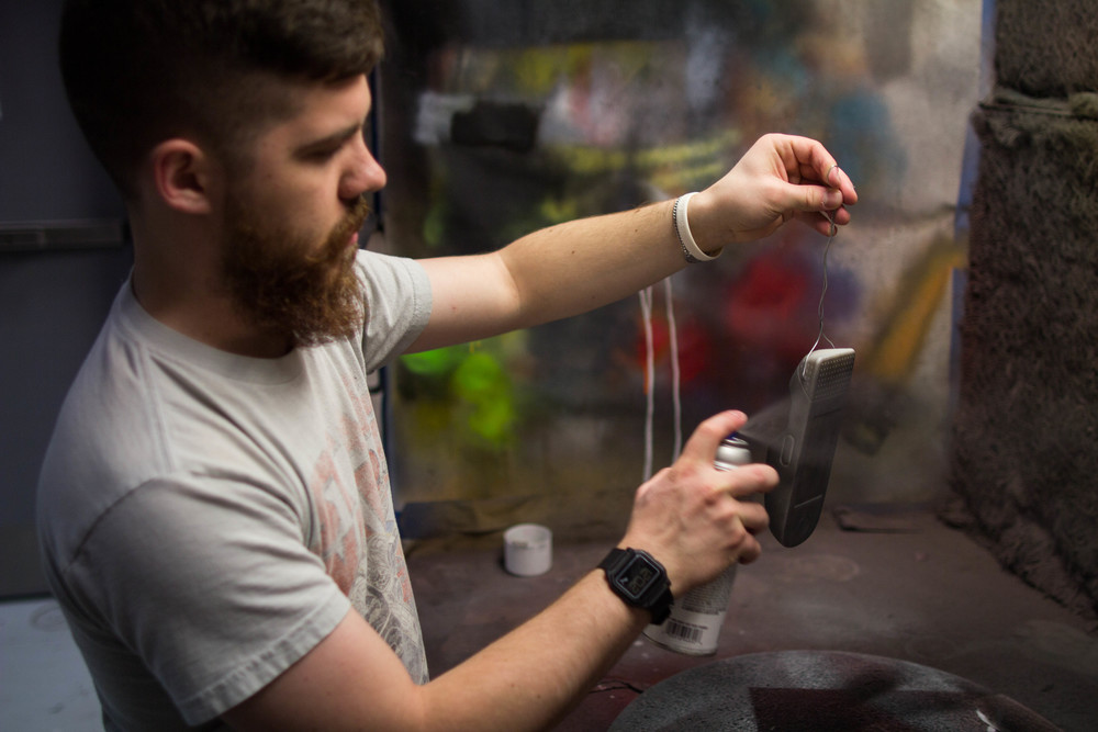 Designer Colin Beney spray-painting the 3-D printed prototype.
