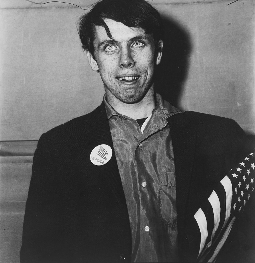 Diane Arbus, Patriotic Young Man with a Flag. NYC, 1967.