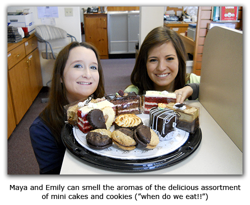 Southgate Coins manager Maya Jones and Emily pose around the anniversary dessert tray