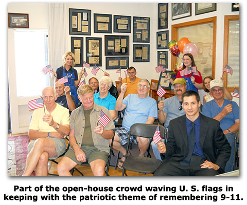 Open house attendees waive American flags at Southgate Coins