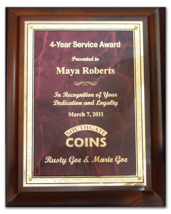 Southgate Coins owners Rusty and Marie Goe honor Maya Roberts on her 4-year anniversary with the coin shop