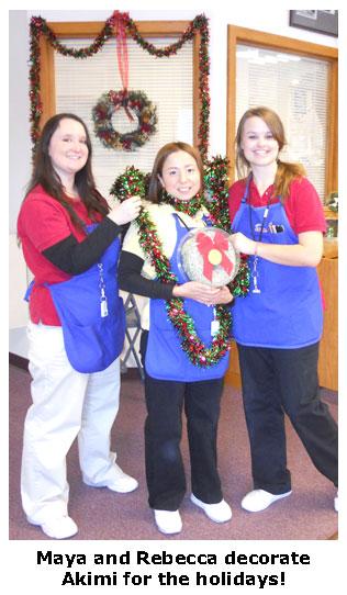 Maya and Rebecca decorate Akimi with holiday garland at Southgate Coins