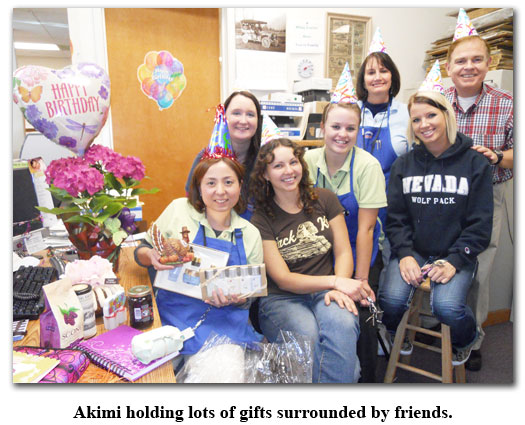 Akimi poses with presents and coworkers for her birthday celebration at Southgate Coins
