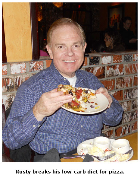 Southgate Coins owner Rusty Goe enjoys his low-carb pizza during the holiday get-together