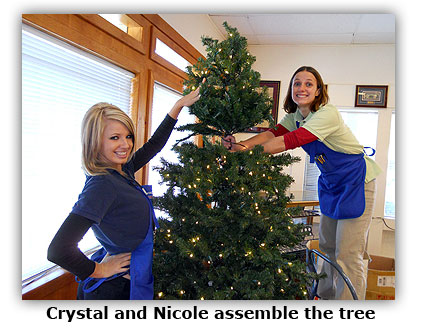 Southgate Coins staffers Nicole and Crystal assemble the Christmas tree