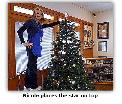 Nicole places the star on top of Southgate Coins' Christmas tree