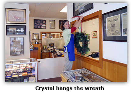 Crystal hangs a wreath at the coin shop