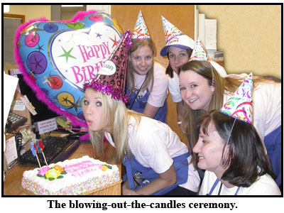 Nicole blows out the candles at her coin shop birthday party