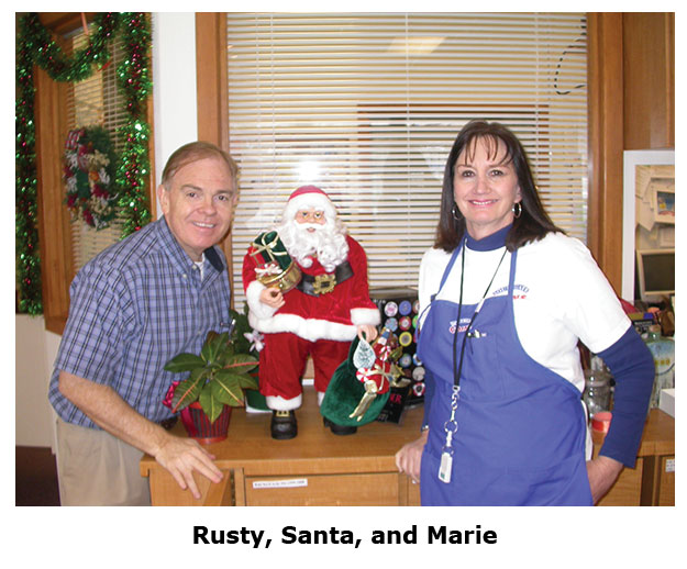 Southgate Coins owners Rusty & Marie Goe pose with a mini Santa
