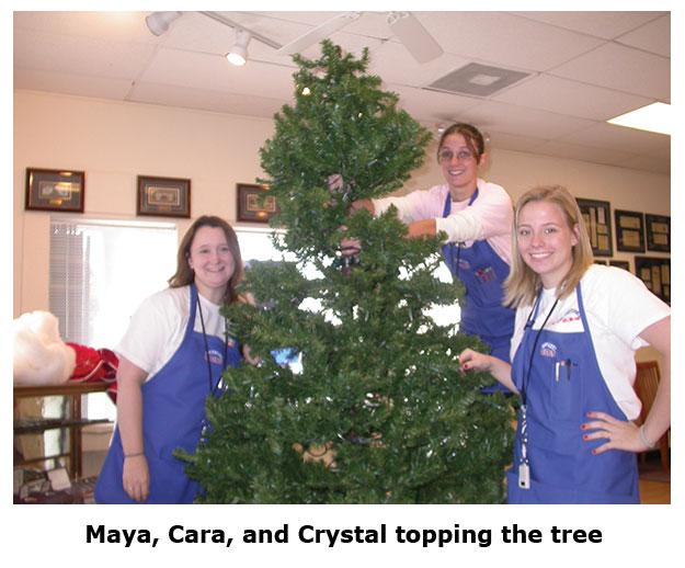 Maya, Cara, and Crystal assemble the coin shop Christmas tree