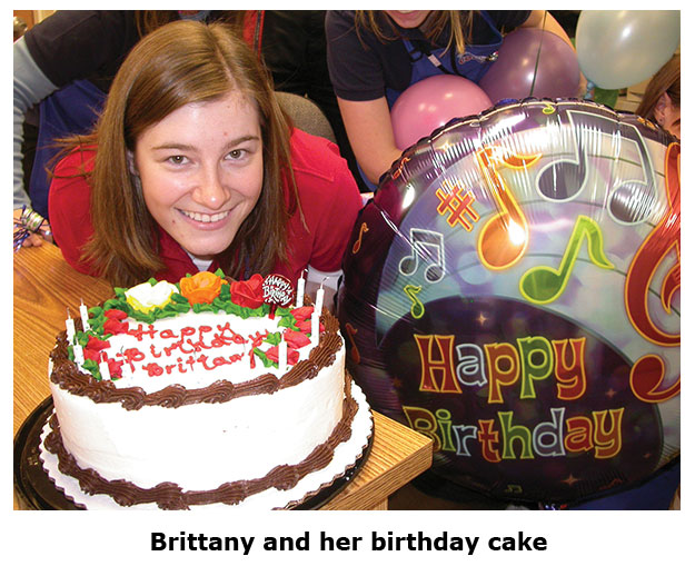 Brittany posing with her cake and balloon at Southgate Coins