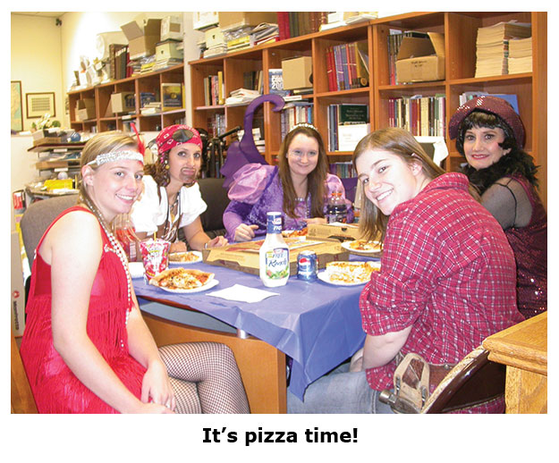 Costumed staffers at the coin shop eat pizza