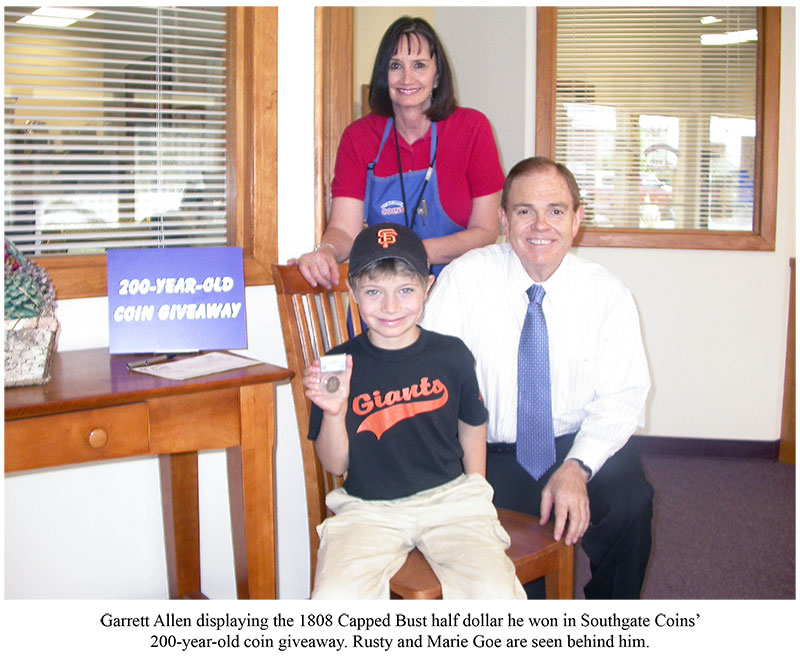 Southgate Coins owners Rusty and Marie Goe pose with Garrett Allen and his prize