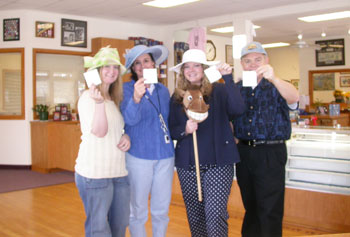 Southgate Coins employees hold up their bets for the Kentucky Derby Day horse race