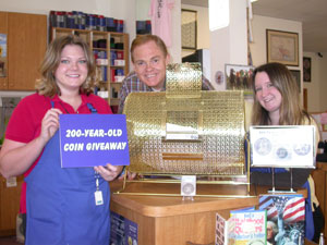 Amy, Rusty, and Maya pose with raffle drum for 200-year-old-coin giveaway