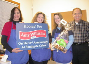 Southgate Coins owners Rusty and Marie Goe present Amy with an achievement sign on her anniversary