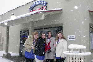 Rachel, Maya, Marie, and Amy pose in front of the coin shop for the first snow of 2008