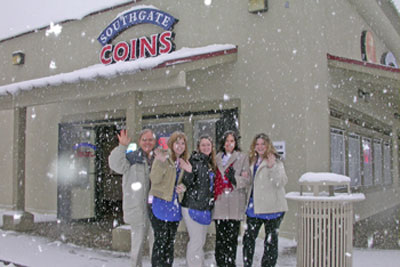 Southgate Coins owners Rusty and Marie and the coin shop staff pose with the snowfall