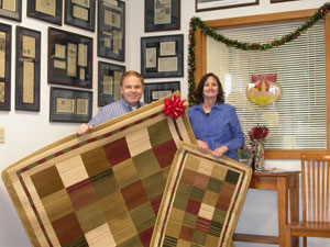 Southgate Coins staff gives owners Rusty and Marie Goe new rugs for the coin shop