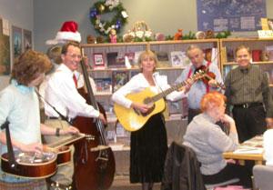 Christmas-caroling musicians visit Rusty Goe at his book signing