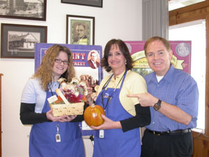 Amy poses with her fall basket with coin shop owners Rusty and Marie Goe
