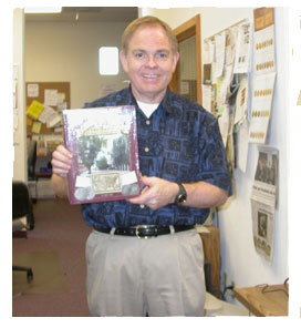 Southgate Coins owner Rusty Goe poses with his new book, James Crawford: Master of the Mint at Carson City