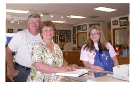 Southgate Coins employee Amy presents her parents with an autographed copy of Rusty's James Crawford book