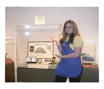 Coin shop employee Amy poses with Nevada State Museum grand prize, donated by Southgate Coins