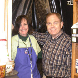 Southgate Coins owners Rusty and Marie Goe pose in front of the plumbing project in the back room.