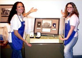 Southgate Coins employees Heather and Amy show off the grand prize at the Nevada State Museum's Carson City Coin Show