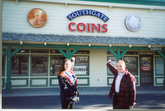 Southgate Coins owner Rusty and employee Heather display the store's lovely 4-foot coin signs