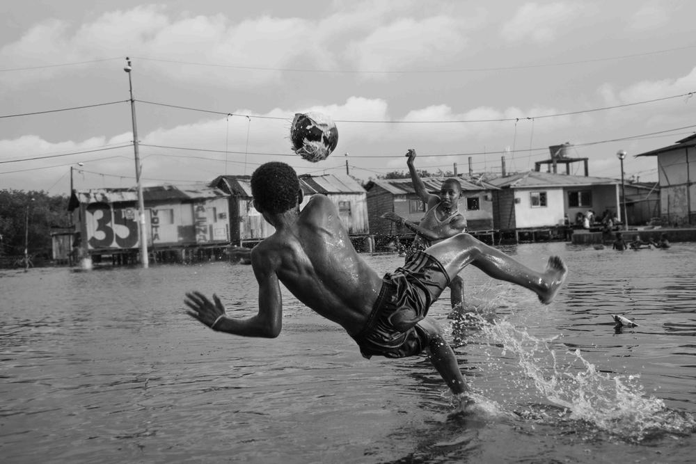 Children play soccer during the monthly high tide that floods the communities for several days in a row. The communities in the Cayapas Mataje Mangrove Reserve have absolutely no sanitation as the tides flood any kind of improved facilities. The water that floods the communities are highly unsanitary. Tambillo, Ecuador. 2014