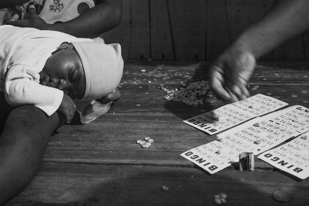 A new born sleeps while her mother plays Bingo with her neighbors. Tambillo, Ecuador. 2014.