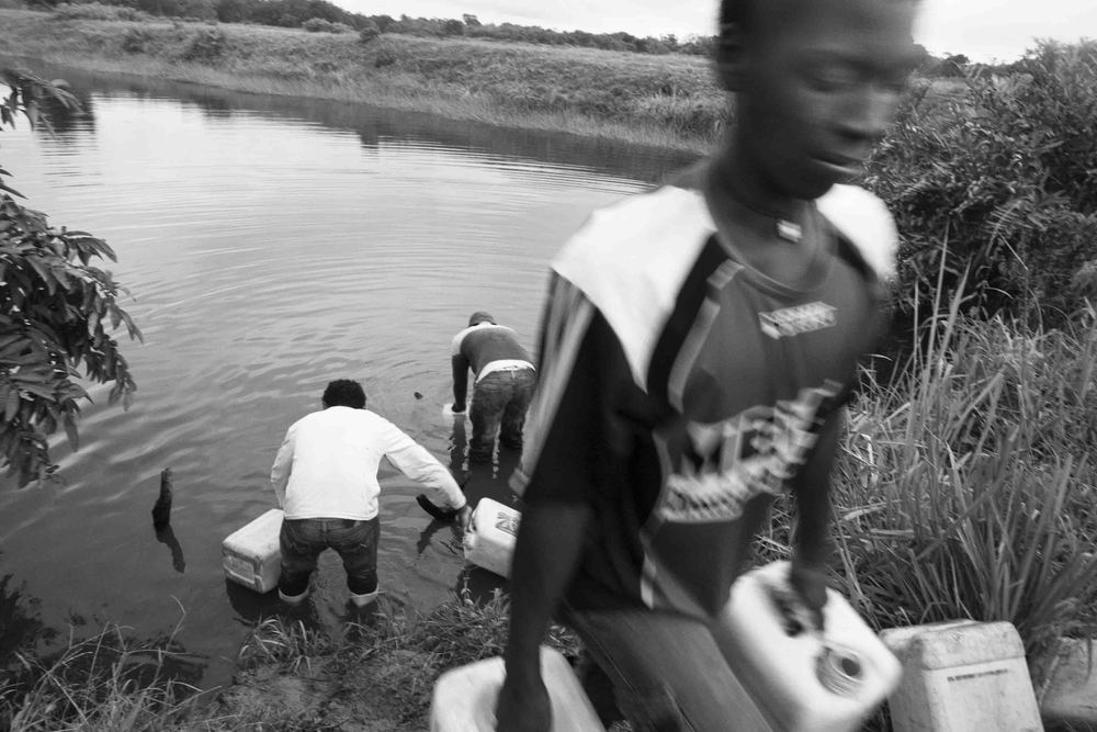 The life of the communities inside the Cayapas Mataje Mangrove Reserve is harsh due to a constant shortage of water. In the picture kids fetch water from a source in a private farm outside the Reserve. Tambillo, Ecuador. 2010.