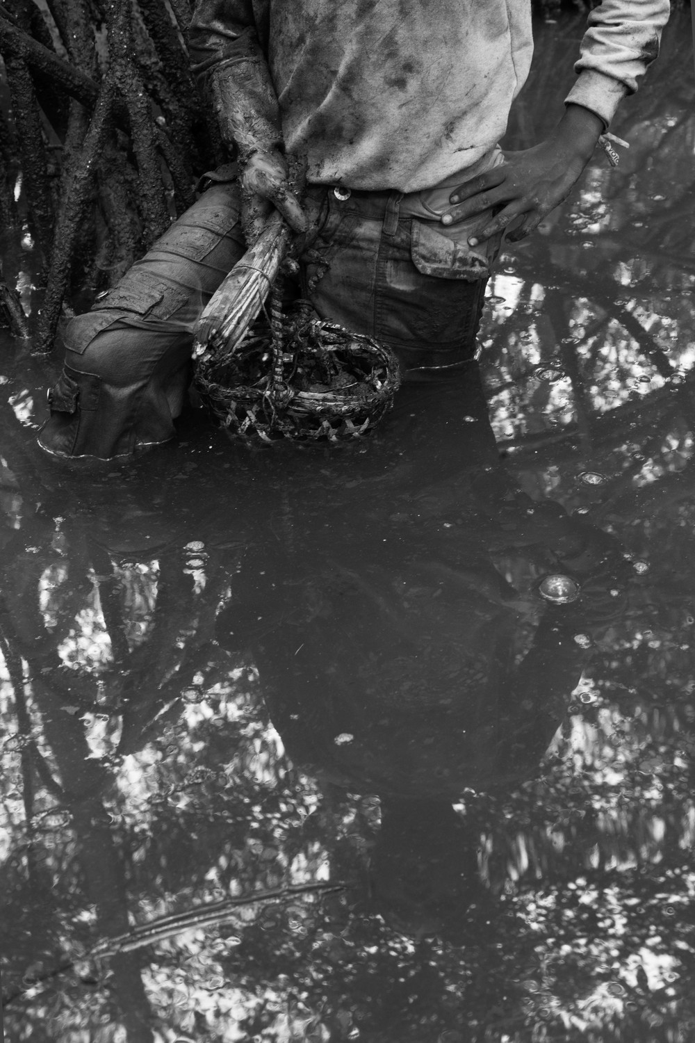 The reflection of Diego Reasco holding his basket and torch can be seen in the water of the Cayapas Mataje Mangrove Reserve. Work days in the mangrove are determined by the ebb and flow of the water. 2014.
