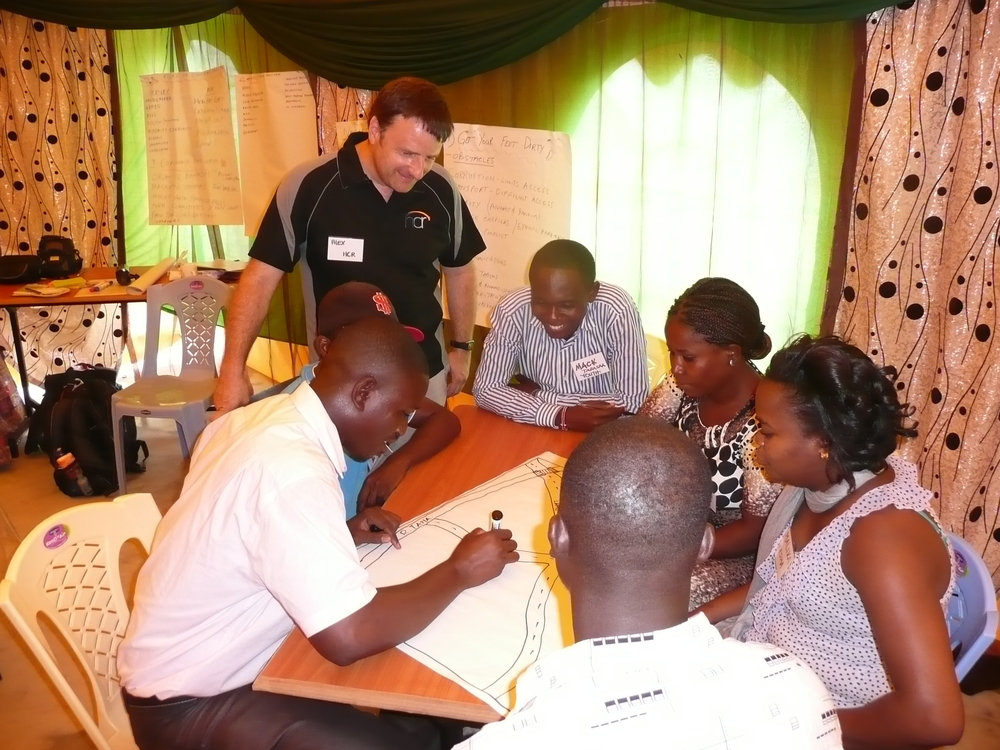 "Alex (left)) and Jon (right) working with local community members on a ""mapping"" activity to identify community needs."