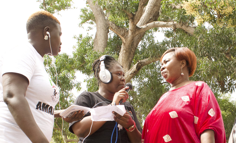 Harriet Atyang and Esther Dalano interview a community member during an Amani FM Road Show
