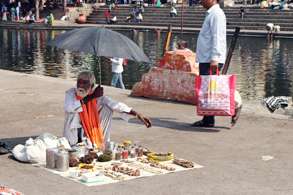 Holy man sells talismans under the shade of an umbrella, while people bathe in the River Ganges