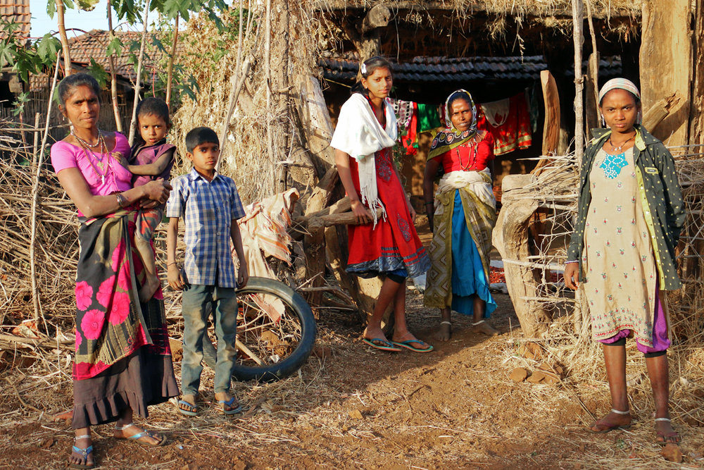 Adivasi family outside their mud and straw house in a typical village in Maharashtra