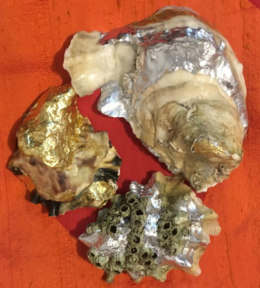"""Novelty Assortment of Oysters """"Rockefeller""""  Fanny Bay Oyster with barnacles adorned with silver leaf, Moonstone accentuated with stripes of silver and gold leaf, Mystery Oyster (TBD) with determined gold leaf."""
